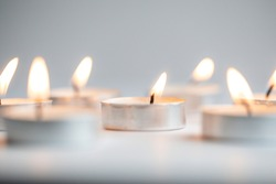 Tea light candles lit with flame on a white background