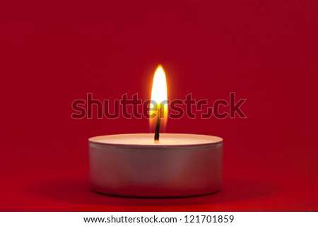 Tea light closeup on red background - stock photo