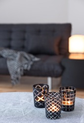 Tea-lights in glass candle holders decorating living room with gray sofa.