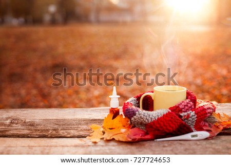 Tea mug covered with warm scarf, thermometer and nose drops on wooden surface with red leaves #727724653