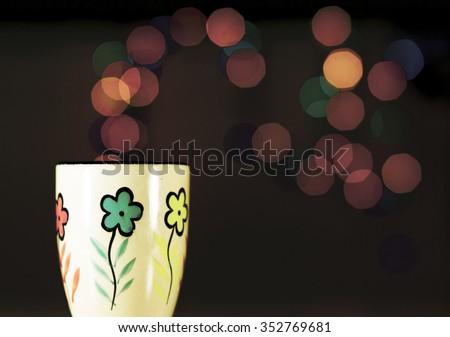 Tea mug on the background bokeh. Ceramic mug stands on the table.
