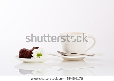 tea or coffee and heart shaped cookie with flower on a plate
