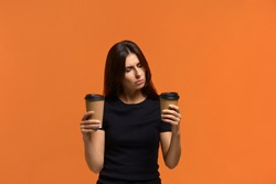 Tea or coffee. Need to cheer up. Confused caucasian woman in black t-shirt chooses between two types of drink in disposable cups. Cappuccino or flat white. Isolated on orange background