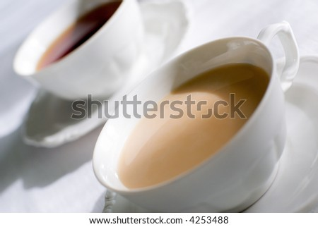 Tea or coffee set - two porcelain cup on the table, one with milk.