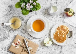 Tea, pancake, apple sauce, homemade gift in kraft paper, flower violet on a light background. Romantic breakfast table. Vintage style, top view