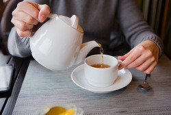 tea pour from the kettle with lemon in a cafe a white cup and saucer