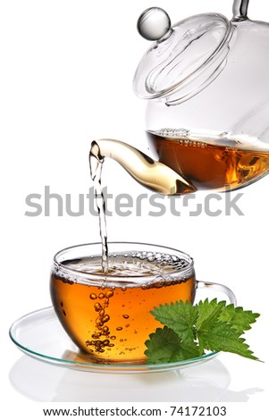 Tea poured into cup on white background