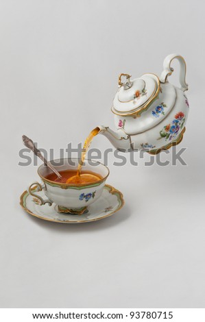 Tea pours into a cup with lemon from teapot