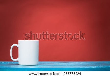 Tea. Red mug on wooden tabletop against grunge green wall