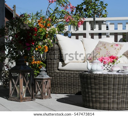 Tea-set and beautiful flowers on sunny terrace. #547473814