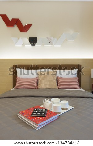 tea set and books decorated on bed.
