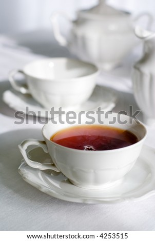 Tea set - two teacups, one with steaming hot tea, sugarbasin behind. Focus on teacup, shallow depth of field.