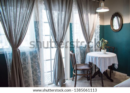 Tea table set with plant pot beside large windows and large gray curtains with sunlight filter. #1385061113