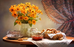 Tea table with vase of flowers. Tea time with flowers. Tea table vase flowers. Tea table and vase of orange flowers