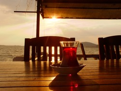 Tea time against the sunset in the Aegean coast, Turkish tea in traditional glass, Aegean islands, wooden table and chairs, sea view from a cafe