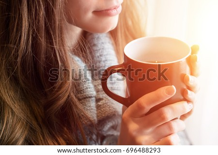Tea time. Beautiful blonde woman holding ceramic cup of tea or coffee enjoy closeup. Looking at window and drink tea. Good morning with tea. Selective focus. Pretty young girl relaxing. Happy concept.