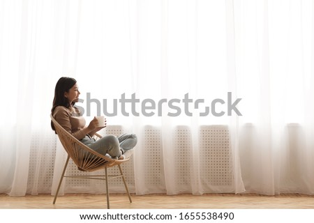Tea time. Relaxed girl sitting in modern chair, enjoying hot coffee in front of window, side view, free space