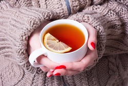 tea with a lemon in woman hand