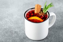 tea with cranberries, cinnamon , orange, rosemary, star anise and honey in a white cup on a gray background
