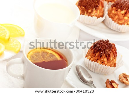 tea with lemon and fancy cakes, still life
