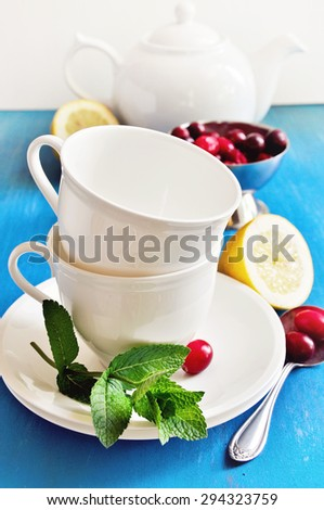 Tea with lemon, mint, and fresh cranberries on a blue background. Table setting for tea time, porcelain cups, table setting for tea time, selective focus