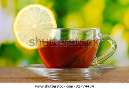 tea with lemon on green leaves background