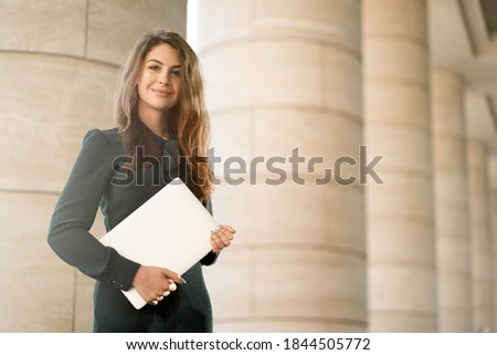 teacher a teacher at the Institute works holding folders with documents reports, posing for the camera. Manager businesswoman brunette woman long hair in a new dress in the shop.