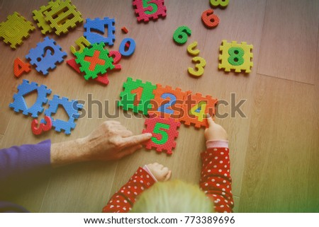 teacher and child play with number puzzle, learning math #773389696