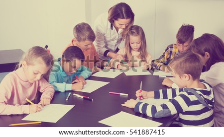 Stock Photo Teacher and elementary age children drawing at classroom in school