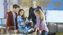 Teacher and His Pupils Work on a Programable Robot with LED Illumination for School Science Class Project.