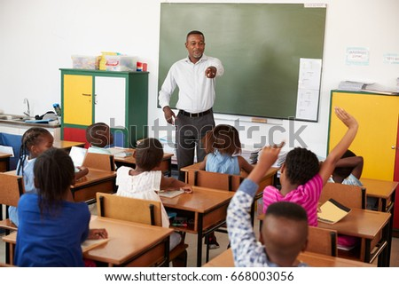 Teacher and kids with hands up in an elementary school class