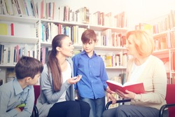 Teacher and mother with sons on meeting at school library