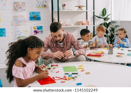 teacher and multiethnic kids sculpturing figures with colorful plasticine at table in classroom