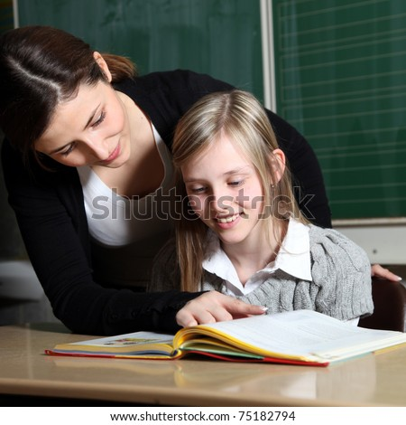 Teacher and pupil in classroom learning together. The girl looks together with the teacher in a book. This tells the child the task. -square