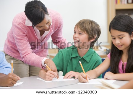 Teacher and pupil in elementary school classroom working on written project