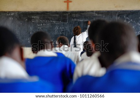 Teacher and pupils at mathematics lesson in a classroom in a school in Africa #1011260566