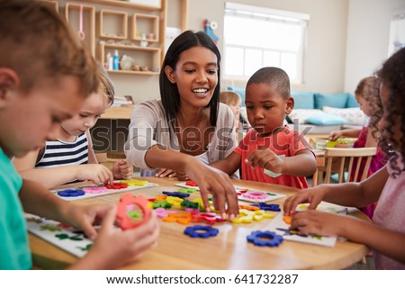 Teacher And Pupils Using Flower Shapes In Montessori School #641732287