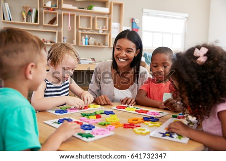 Teacher And Pupils Using Flower Shapes In Montessori School #641732347