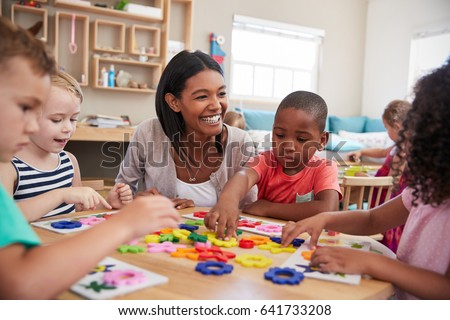 Teacher And Pupils Using Flower Shapes In Montessori School #641733208
