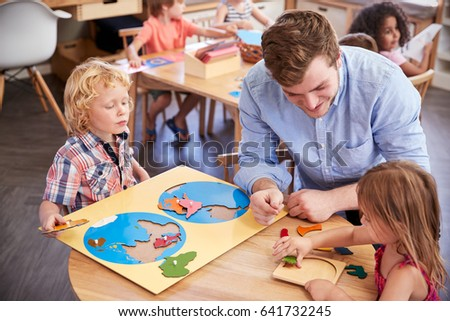 Teacher And Pupils Using Wooden Shapes In Montessori School #641732245