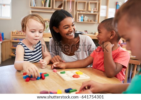 Teacher And Pupils Using Wooden Shapes In Montessori School #641754301