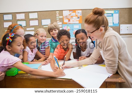 Teacher and pupils working at desk together at the elementary school Сток-фото ©