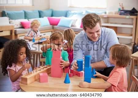 Teacher And Pupils Working At Tables In Montessori School #640434790