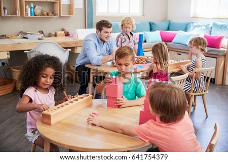 Teacher And Pupils Working At Tables In Montessori School #641754379