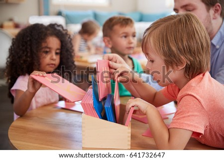 Teacher And Pupils Working With Letters In Montessori School #641732647