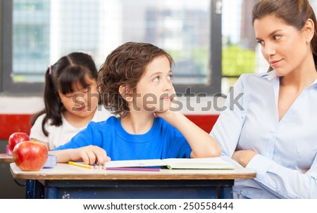 Teacher and schoolboy looking each other in primary classroom