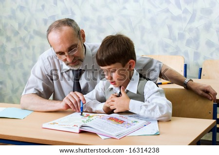 Teacher and schoolboy read alphabet. Primary school.