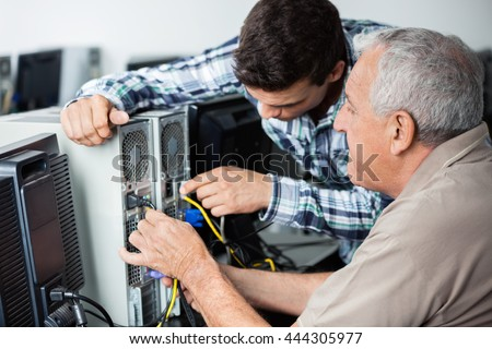 Teacher And Senior Man Fixing Computer In Class