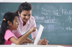 teacher and student at laptop, girl pointing at screen