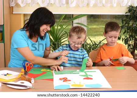 teacher and two preschoolers making some decoration